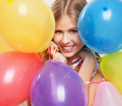 Beautiful girl holds set of colored balloons